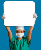 Doctor with a Blank Board. A young woman doctor in a mask holding an empty bill board over her head against a blue background Royalty Free Stock Images
