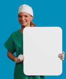 Doctor with a Blank Board. A smiling young woman doctor holding an empty white bill board against a blue background Royalty Free Stock Images