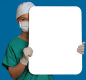 Doctor with a Blank Board. A smiling young woman doctor holding an empty white bill board against a blue background Royalty Free Stock Photos