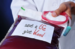 Doctor with a blood bag with the text safe a life give blood Stock Photos