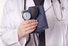 Doctor and blood pressure. Doctor standing with blood pressure gauge, sphygmomanometer, in the hand, ready for the medical check up stock image