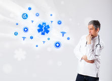 Doctor with blue medical icons Royalty Free Stock Photo