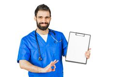 Doctor in blue robe with stethoscope pointing to clipboard isolated on white background stock images