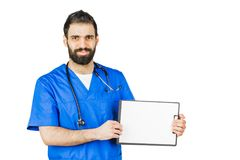 Doctor in blue robe with stethoscope pointing to clipboard isolated on white background stock photography