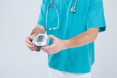 The doctor is holding a electronic tonometer. Isolation. Close up. The doctor in blue uniform is holding a modern electronic tonometer. Isolation. Close up Royalty Free Stock Photography