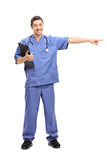 Doctor in blue uniform pointing right Stock Photography