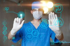 Doctor in blue uniform touch display with infographics. Modern professional surgeon in the operating room. Medical icons on the desktop Stock Image