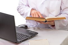 Doctor with book and laptop. Doctor with a great book and a laptop on the table Stock Image