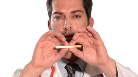 Doctor breaking a cigarette stock footage