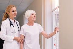 Doctor brillante atento que camina abajo del pasillo con su paciente Foto de archivo libre de regalías