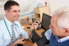 Doctor británico que toma la presión arterial del hombre Foto de archivo libre de regalías