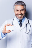 Doctor with business card. Confident mature doctor showing his business card and smiling while standing against grey background Royalty Free Stock Image