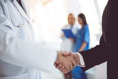 Doctor and businessman. Cropped image of handsome mature doctor and young businessman shaking hands while standing in the hospital hall Royalty Free Stock Images
