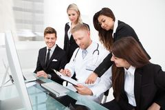 Doctor and businesspeople discussing over clipboard. Male doctor and businesspeople discussing over clipboard at desk in office stock photos