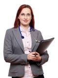 Doctor cómodo de la señora con el estetoscopio y las notas Fotos de archivo libres de regalías