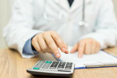 Doctor is calculating cost of treatment Royalty Free Stock Images