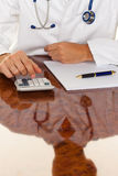 Doctor with a calculator. Costing medical practice stock photo