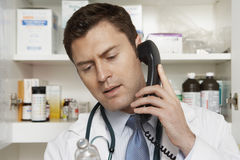 Doctor On Call While Looking At Drug Bottle Stock Image