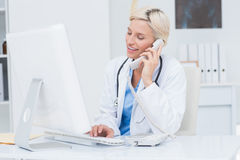 Doctor on call while using computer in clinic Royalty Free Stock Images