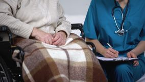 Doctor on call visiting elderly patient at home, writing in medical records