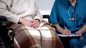 Doctor on call visiting elderly patient at home, writing in medical records stock photos