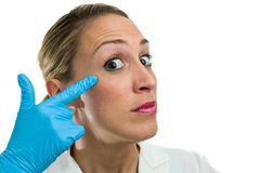 Doctor calling attention. Young female doctor or plastic surgeon pointing his eye, calling attention, isolated in white background Royalty Free Stock Image
