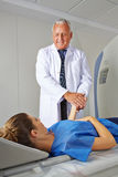 Doctor calming patient on MRI machine Stock Photo