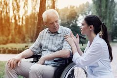 The doctor calms the sad old man sitting on a wheelchair. Doctor calms a sad old men sitting on a wheelchair in a summer park royalty free stock photo
