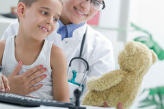 Doctor calms a young boy in office Stock Image