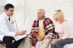 A doctor came to the old man in a yellow cardigan. The old man became ill and the doctor diagnoses him. A doctor came to the old men in a yellow cardigan. The royalty free stock photo