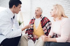 A doctor came to the old man in a yellow cardigan. The old man became ill and the doctor diagnoses him. A doctor came to the old men in a yellow cardigan. The royalty free stock photography