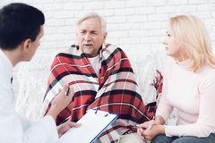 A doctor came to the old man in a yellow cardigan. The old man became ill and the doctor interrogates him. A doctor came to the old men in a yellow cardigan royalty free stock photography
