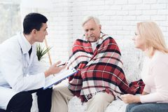 A doctor came to the old man in a yellow cardigan. The old man became ill and the doctor interrogates him. A doctor came to the old men in a yellow cardigan stock photo