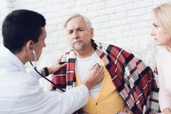 A doctor came to the old man in a yellow cardigan. Doctor listens to his heart with a stethoscope. A doctor came to the old men in a yellow cardigan. The old stock image