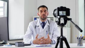 Doctor with camera recording video blog at clinic