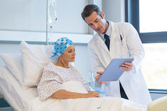 Doctor with cancer patient. Doctor telling to patient women the results of her medical tests. Doctor showing medical records to cancer patient in hospital ward stock photos