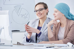 Doctor and cancer patient. Young doctor talking with her cancer patient in an office Stock Images