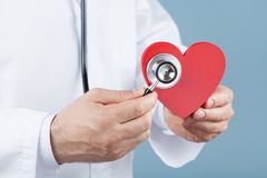 Doctor cardiologist holding a red heart in his hands and stethoscope. Cardiology and heart disease concept. royalty free stock photography