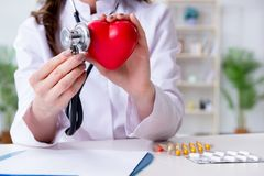 The doctor cardiologist with red heart in the hospital Stock Photos