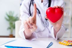 The doctor cardiologist with red heart in the hospital Stock Image