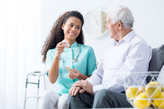 Doctor caring about elder person Stock Photos