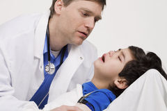 Doctor caring for a sick little boy Stock Image