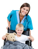 A doctor carrying a little boy. Nice female doctor carrying adorable little boy in the wheelchair at the hospital Royalty Free Stock Photo