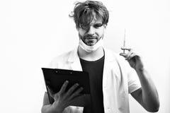 Doctor caucásico barbudo o estudiante graduado con el tablero y la jeringuilla imagen de archivo