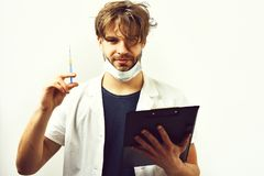 Doctor caucásico barbudo o estudiante graduado con el tablero y la jeringuilla imagenes de archivo