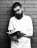 Doctor caucásico brutal barbudo o estudiante graduado con el cuaderno imágenes de archivo libres de regalías
