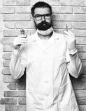 Doctor caucásico brutal barbudo o estudiante graduado que sostiene píldoras fotos de archivo libres de regalías