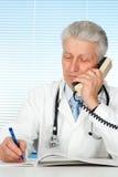 Doctor caucásico feliz con una sentada del teléfono Fotografía de archivo libre de regalías