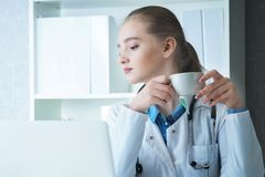 Doctor cauc?sico de sexo femenino joven que tiene una rotura y que bebe el caf? que se sienta en su lugar de trabajo fotografía de archivo