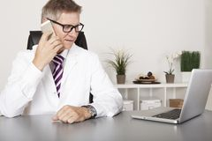 Doctor chatting on his mobile phone Royalty Free Stock Image